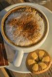 Café del capuchino en una taza blanca con cinnamone y las galletas Imagen de archivo