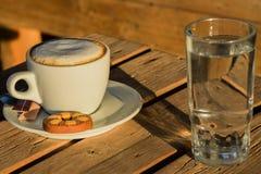 Café del capuchino en una taza blanca con cinnamone y las galletas en un vidrio de agua Imagenes de archivo
