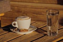 Café del capuchino en una taza blanca con cinnamone y las galletas en un vidrio de agua Fotos de archivo libres de regalías