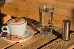 Café del capuchino en una taza blanca con cinnamone y las galletas en un vidrio de agua Imagen de archivo libre de regalías