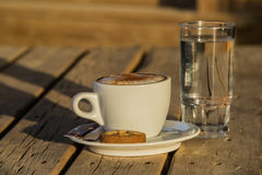 Café del capuchino en una taza blanca con cinnamone y las galletas en un vidrio de agua Fotografía de archivo