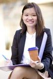 Café del ejecutivo de sexo femenino asiático joven y fichero de tenencia de consumición Foto de archivo libre de regalías