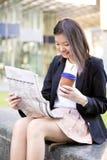 Café del ejecutivo de sexo femenino asiático joven y periódico de consumición de la lectura Imagenes de archivo