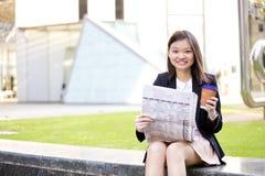 Café del ejecutivo de sexo femenino asiático joven y periódico de consumición de la lectura Imagen de archivo libre de regalías