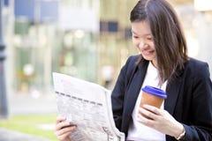 Café del ejecutivo de sexo femenino asiático joven y periódico de consumición de la lectura Imagen de archivo
