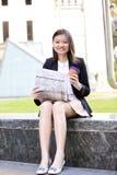 Café del ejecutivo de sexo femenino asiático joven y periódico de consumición de la lectura Fotografía de archivo