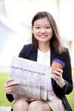 Café del ejecutivo de sexo femenino asiático joven y periódico de consumición de la lectura Fotos de archivo libres de regalías
