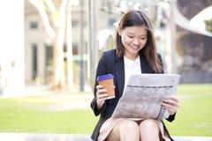 Café del ejecutivo de sexo femenino asiático joven y periódico de consumición de la lectura Foto de archivo