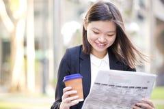 Café del ejecutivo de sexo femenino asiático joven y periódico de consumición de la lectura Fotos de archivo