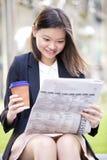 Café del ejecutivo de sexo femenino asiático joven y periódico de consumición de la lectura Imágenes de archivo libres de regalías