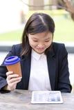 Café del ejecutivo de sexo femenino asiático joven y tableta de consumición con Imágenes de archivo libres de regalías