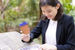 Café del ejecutivo de sexo femenino asiático joven y tableta de consumición con Foto de archivo libre de regalías