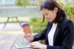 Café del ejecutivo de sexo femenino asiático joven y tableta de consumición con Imagen de archivo
