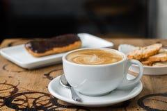 Café del flatwhite del capuchino con el eclair Foto de archivo libre de regalías