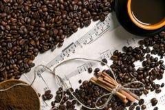 Café del grano de café, molido y taza de café preparado en el fondo de la partitura, visión desde arriba con el espacio para el t Imágenes de archivo libres de regalías