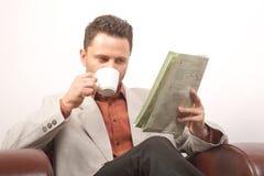 Café del hombre y periódico de consumición de la lectura Imágenes de archivo libres de regalías