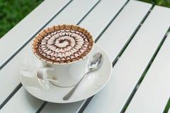 Café del modelo del diseño en una taza blanca Imagen de archivo libre de regalías
