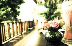 Café del smoothie de la fresa en el fondo del vintage del florero del foco del borde de la terraza Fotos de archivo
