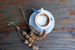 Café do cappuccino no copo branco com colher de café e tamarindo na tabela de madeira imagens de stock royalty free