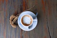 Café do cappuccino no copo branco com colher de café e tamarindo na tabela de madeira imagem de stock royalty free
