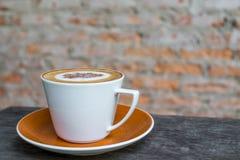 Café do cappuccino no copo branco na tabela de madeira com o wa velho do tijolo Imagens de Stock