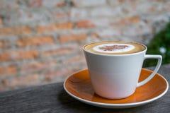 Café do cappuccino no copo branco na tabela de madeira com o wa velho do tijolo Fotografia de Stock