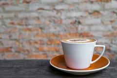 Café do cappuccino no copo branco na tabela de madeira com o wa velho do tijolo Fotos de Stock