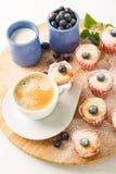 Café do café da manhã com os mini queques e mirtilos em um suporte de madeira fotos de stock royalty free