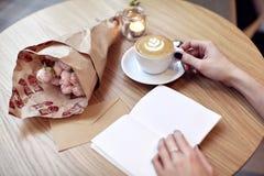 Café do latte do cappuccino na mão da mulher com coração na parte superior Café do latte de FlowersCappuccino na mão da mulher co Imagens de Stock