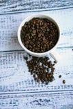 Café dos feijões de café no fundo de madeira da caneca branca Fotos de Stock