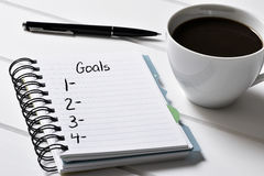 Café e caderno com uma lista vazia de objetivos imagem de stock