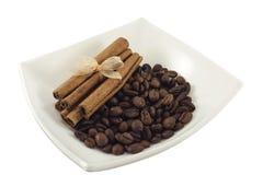 Café e canela em uma placa branca imagem de stock