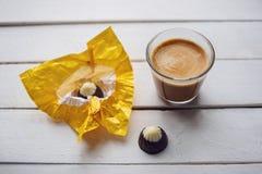 Café e chocolates na tabela de madeira branca Fotografia de Stock