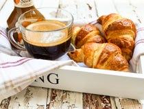 Café e croissant na bandeja de madeira imagem de stock royalty free