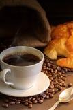 Café e croissant quentes na tabela de madeira Foto de Stock