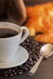 Café e croissant quentes na tabela de madeira Imagens de Stock