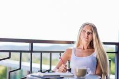 Café e escrita da bebida da jovem mulher no jornal do livro de nota no caf fotos de stock