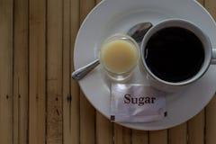 Café e leite condensado e açúcar Foto da opinião de tampo da mesa do café da manhã da manhã Tabela de madeira rústica com copo de fotografia de stock royalty free