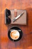 Café e máscaras da pena do caderno na tabela de madeira Imagens de Stock Royalty Free