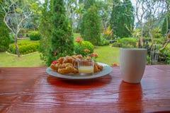 Café e phongko quentes com leite condensado na tabela de madeira vermelha na parte dianteira do terraço fotos de stock