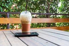 Café e smartphone congelados na tabela de madeira Imagem de Stock Royalty Free