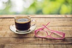 Café e vidros em uma tabela de madeira com um bokeh do fundo Imagem de Stock