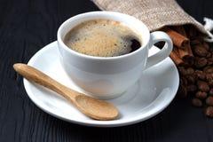 Café em um copo branco com uns pires e uma colher de madeira em um fundo preto com um saco de feijões de café Imagens de Stock