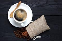 Café em um copo branco com uns pires e uma colher de madeira em um fundo preto com um saco de feijões de café Foto de Stock
