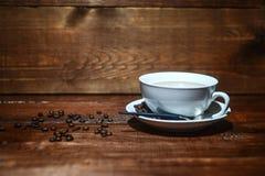 Café em um copo branco em um fundo de madeira escuro com feijões de café imagem de stock