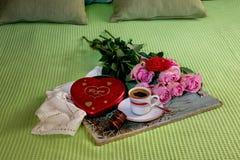 Café em um copo, em rosas e em uma caixa dos chocolates em uma tabela de madeira fotos de stock royalty free