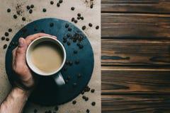 Café em um ralador com um copo à disposição em um fundo escuro com creme fotografia de stock royalty free