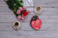 Café em uns copos, em umas rosas e em uma caixa dos chocolates em uma tabela de madeira Fotos de Stock Royalty Free