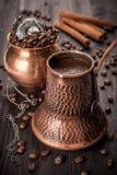 Café en el crisol, los granos de café y los relojes del vintage. Todavía vida. Imagen de archivo libre de regalías