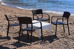 Café en la playa: tabla y sillas de mimbre por el mar Imagenes de archivo